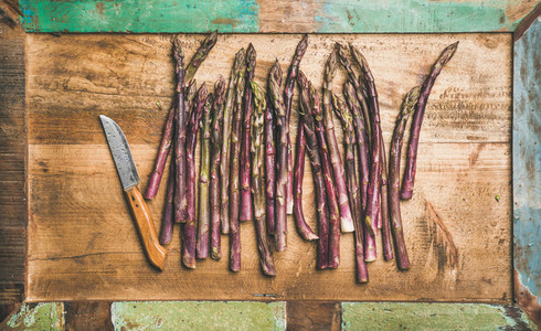 Fresh purple asparagus over wooden tray background