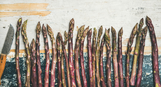 Fresh Raw uncooked purple asparagus over rustic wooden background
