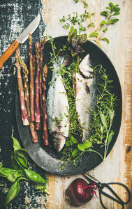 Raw uncooked sea bass fish with herbs and asparagus