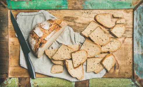 Flat lay of sourdough wheat bread cut in slices in tray