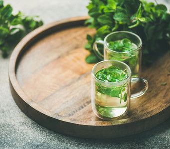 Hot herbal mint tea in glass mugs on wooden tray