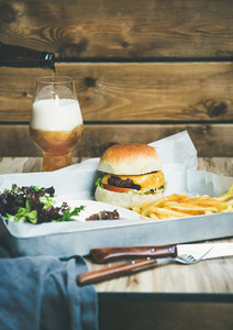 Beef burger french fries salad and glass of beer