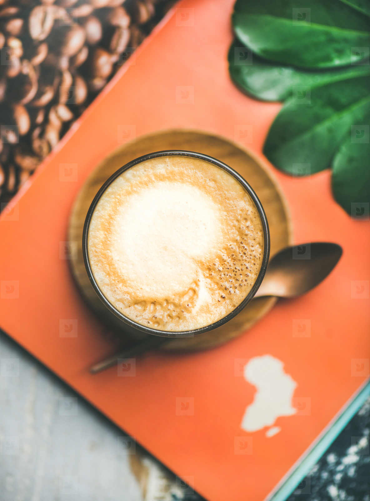Cappuccino coffee in glass over table with magazine background