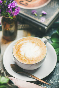 Classic foamy cappuccino coffee in cup with flowers selective focus