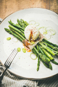 Green asparagus with soft boiled egg in white plate selective focus