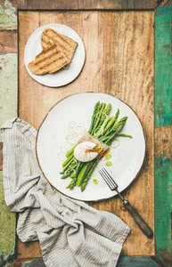 Flat lay of green asparagus  soft boiled egg   bacon  leek and toasts