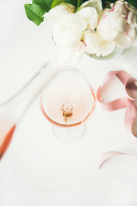 Rose wine in glass  pink ribbon  peony flowers  vertical composition