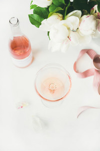 Rose wine in glass  pink ribbon  peony flowers  top view