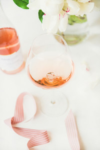 Rose wine in glass and bottle  pink ribbon  peony flowers