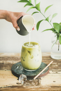 Iced matcha latte drink with milk pouring from pitcher