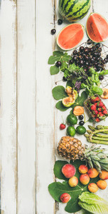 Seasonal fruit  vegetables and greens over wooden background  vertical composition