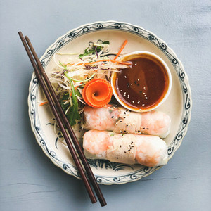 Asian style dinner Flat lay of steamed dumplings Dim sum and summer rice paper rolls with shrimp and sauce over blue table top view copy space Chinese cuisine