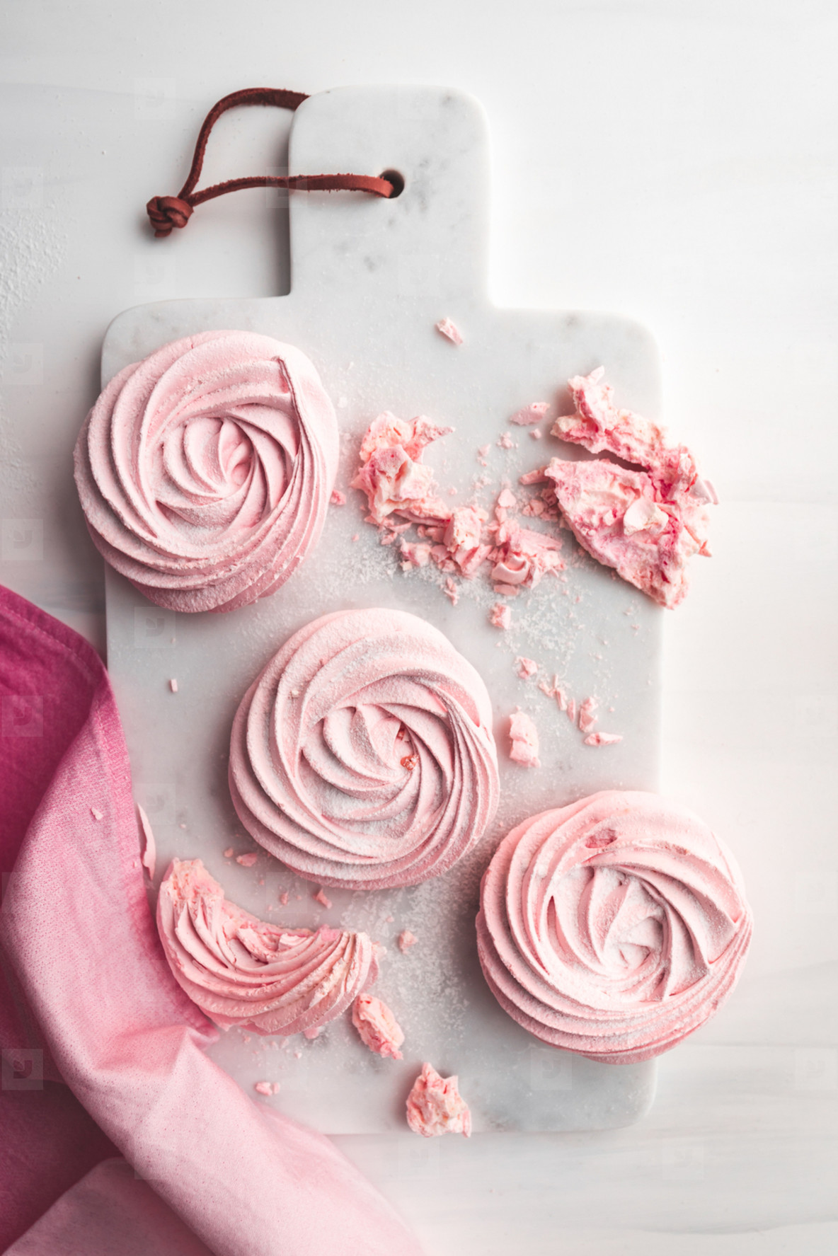 Top view of pink meringue on a white marble tray  Flat lay composition
