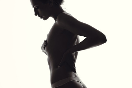 Silhouette of sensual female covering her breast