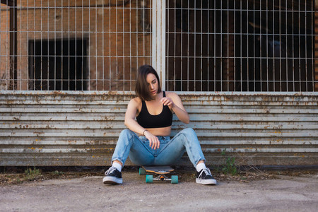 Young woman sitting on her skate in an old industrial street