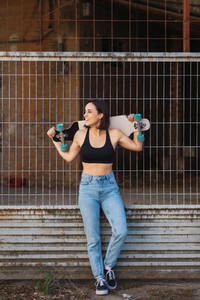 Young woman skater smiling holding her longboard behind her head