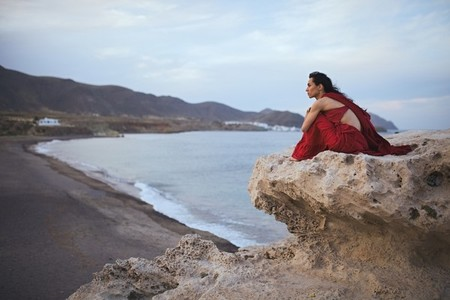 Young brunette woman dancer resting in a rock near the beach