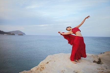 Young brunette woman dancing above a rock near sea coast