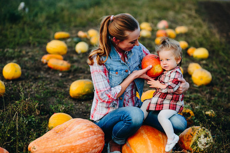 Mother and daughter sitting on pumpkins