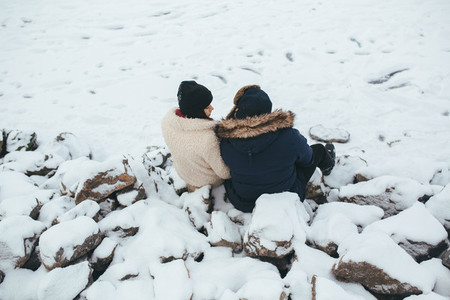 man and woman sitting on the snow covered rocks