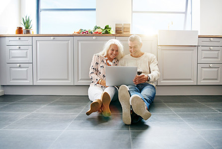 Senior couple drinking wine and using a laptop at home