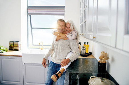 Smiling senior couple sharing a moment in their kitchen