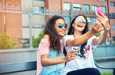 Pair of young friends taking photos near building