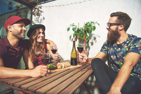Bearded man with couple drinking wine
