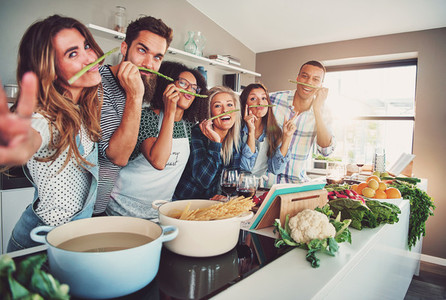 Group of friends fooling with asparagus
