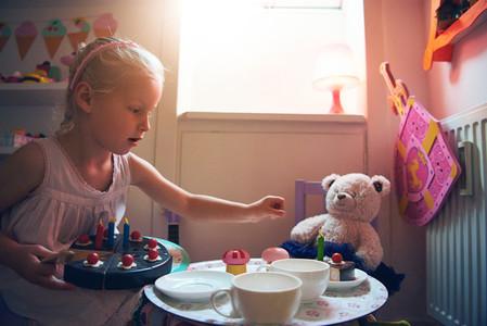 Girl putting slice of cake to bear