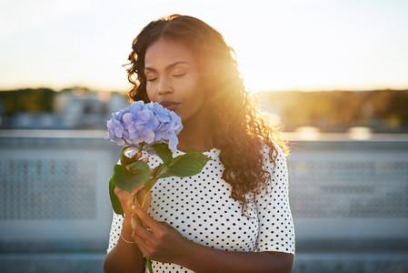 Black woman enjoying a pretty flower