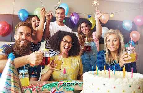 Friends holding drinks at birthday celebration