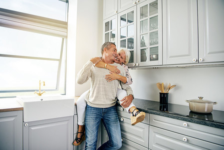 Laughing senior couple sharing a romantic moment in their kitchen