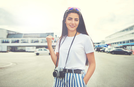 Cute woman with SLR camera standing in street