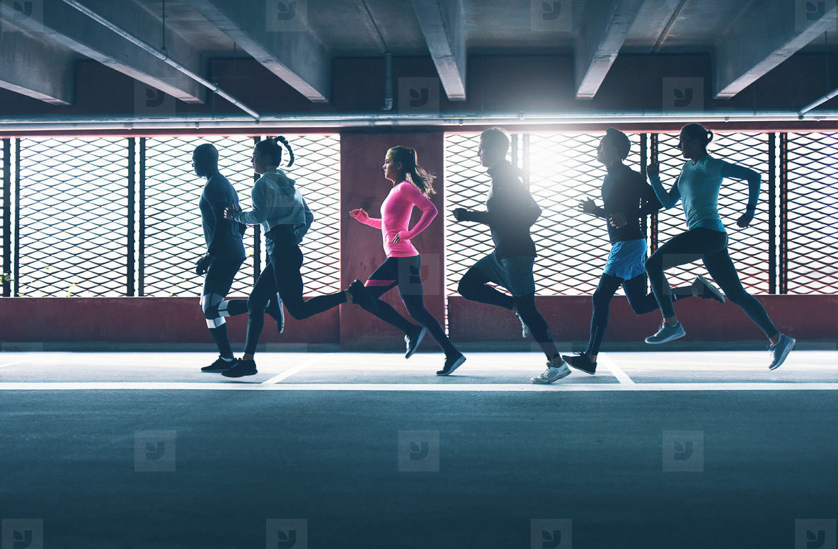 Group of diverse urban runners in a car park
