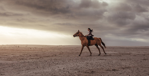 Woman horse ride on beach at sunset