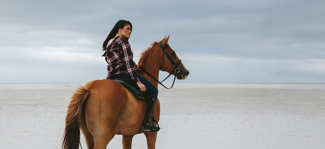Cowgirl riding on horse at beach