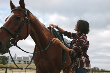 Equestrian woman preparing horse for ride