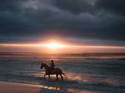Female riding horse along the beach