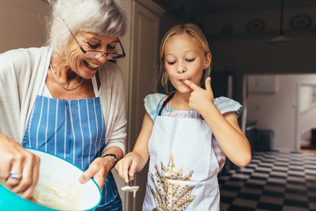 Grandmother and kid having fun making cake in kitchen