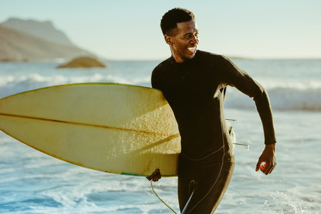 Smiling african male surfer