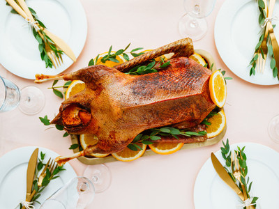 Festive table setting with whole roasted goose on a golden tray for celebrate event or Christmas family dinner Top view flat lay