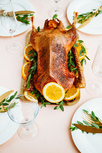 Festive table setting with whole roasted goose on a golden tray for celebrate event or Christmas family dinner