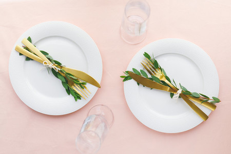 Festive table setting for celebrate event or family dinner with two plates and golden cutlery  Top view  flat lay