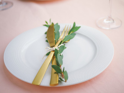 Festive table setting for celebrate event or dinner with white plate and golden cutlery on a pink tablecloth
