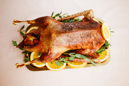 Whole roasted goose with oranges on a golden tray for celebrate event or Christmas family dinner