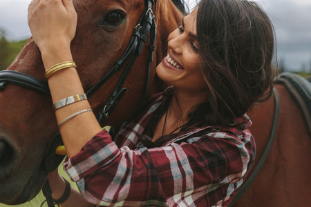 Smiling woman petting her horse