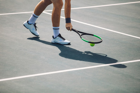 Tennis player picking up the ball