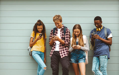 Teenage boys and girls using cell phones standing outdoors