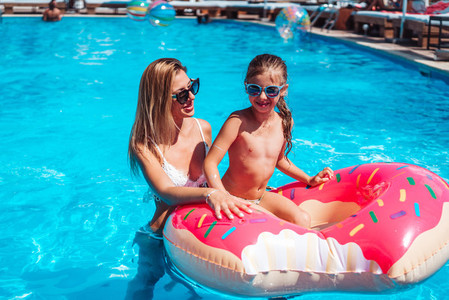 Little girl with her mom in swimming pool